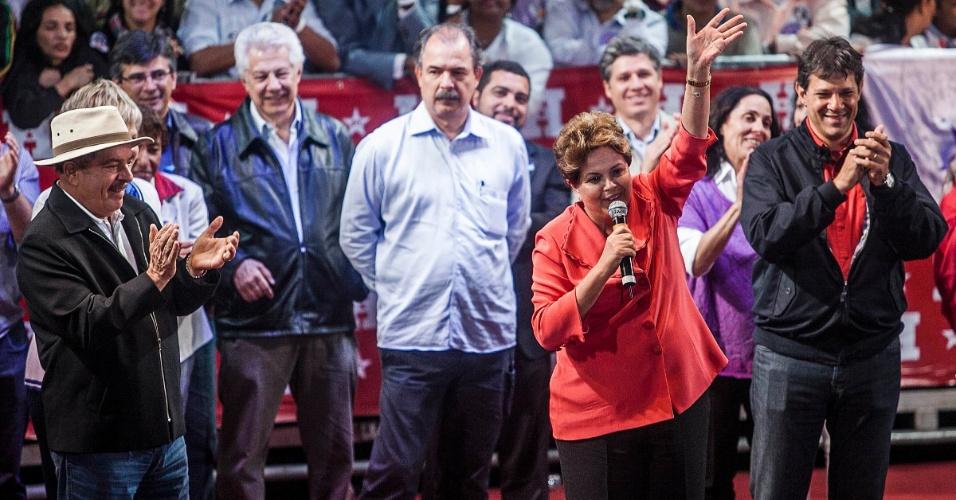 1º.out.2012 - A presidente Dilma Rousseff (de vermelho) e o ex-presidente Luiz Inácio Lula da Silva (à esq.) participam de comício do candidato do PT a prefeito de São Paulo, Fernando Haddad (de camisa vermelha), na zona leste da capital. Dilma retrucou a afirmação de José Serra (PSDB), dizendo que está 'metendo o bico na eleição de São Paulo'. Foi a estreia dela em palanques eleitorais este ano