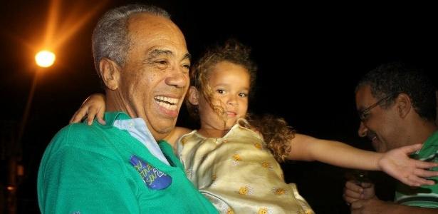 João Alves Filho (DEM) carrega uma criança durante caminhada de campanha em Aracaju