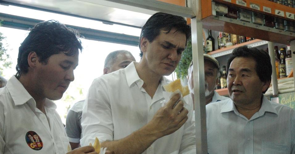 3.out.2012 - O candidato do PMDB à Prefeitura de São Paulo, Gabriel Chalita come um pastel enquanto faz campanha pelo comércio da Saúde, na zona sul da capital paulista, nesta quarta-feira