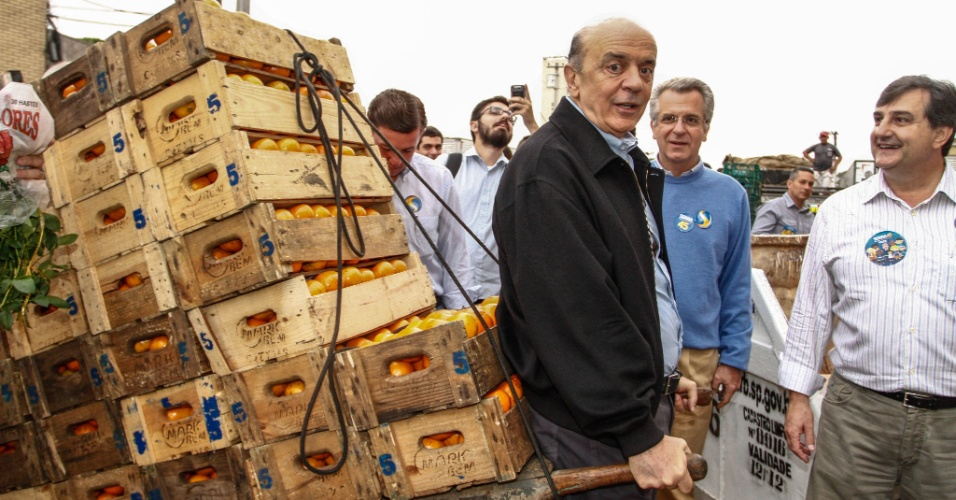 5.out.2012 - O candidato do PSDB à Prefeitura de São Paulo, José Serra, puxa um carrinho de mão carregado com caixas de laranja, durante visita à Ceagesp (Companhia de Entrepostos e Armazéns Gerais de São Paulo)