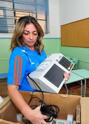 Funcionária começa a instalar a urna eletrônica para as eleições de 2012