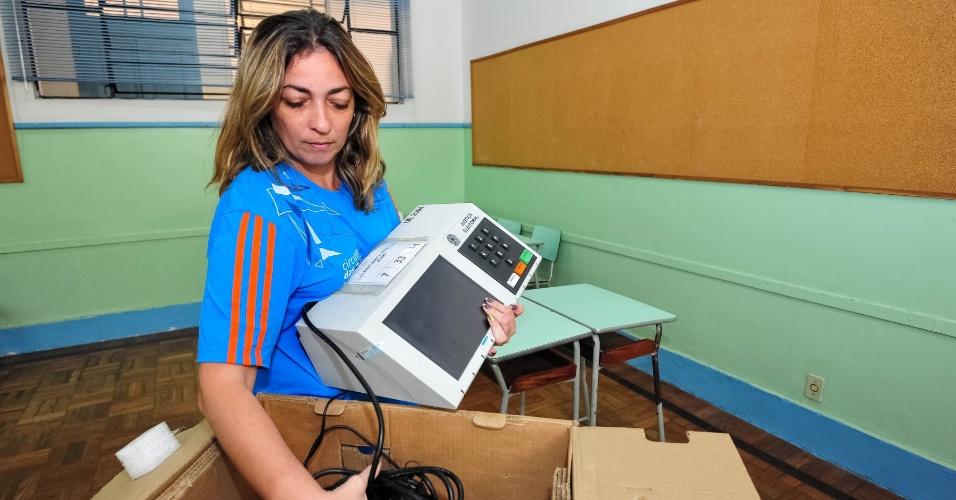 6.out.2012 - Funcionária responsável por seção eleitoral no Rio de Janeiro começa a instalar a urna eletrônica para as eleições de domingo (7)