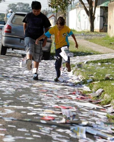 07.out.2012 - Crianças brincam com santinhos eleitorais jogados nos arredores do colégio Estadual Senhorinha de Moraes Sarmento, no bairro Cajuru, maior colégio eleitoral de Curitiba (PR)