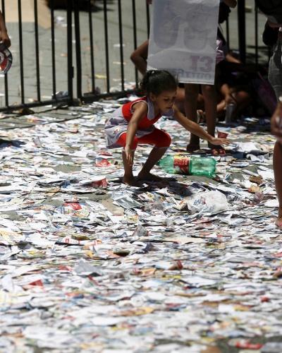 7.out.2012 - Criança se diverte com santinhos espalhados pela avenida Cardeal da Silva em Salvador (BA)