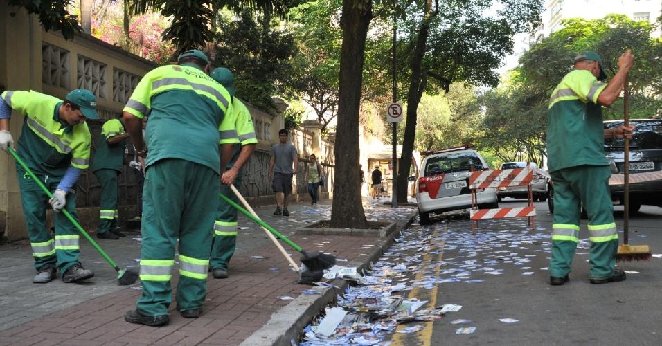 7.out.2012 - Garis recolhem lixo eleitoral jogado próximo de colégio eleitoral na avenida Higienópolis, em São Paulo, neste domingo (7)