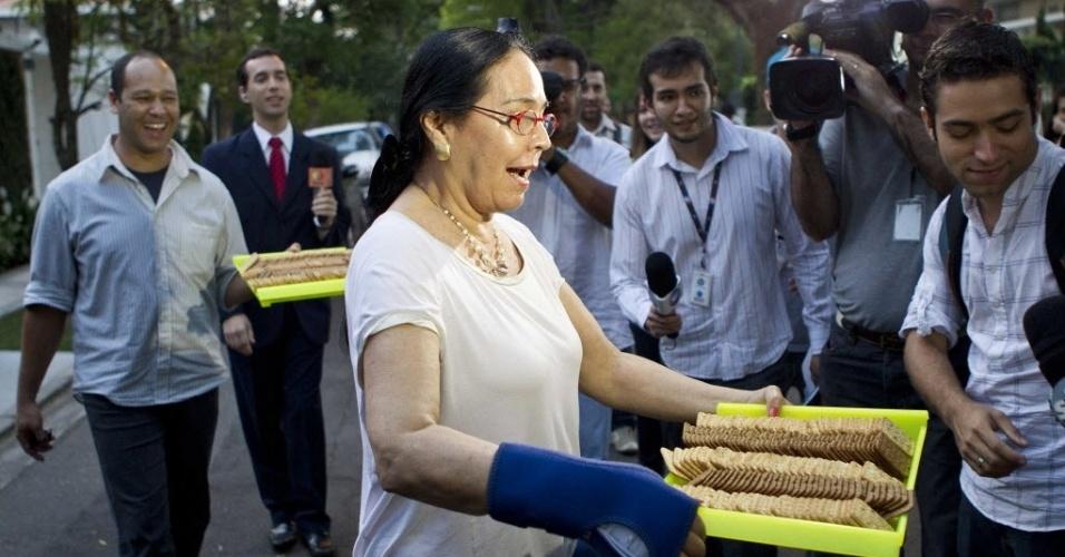 7.out.2012 - Monica Serra, mulher do candidato José Serra (PSDB), oferece bolachas para a imprensa em frente a sua casa no bairro Alto de Pinheiros, em São Paulo, durante apurações do primeiro turno