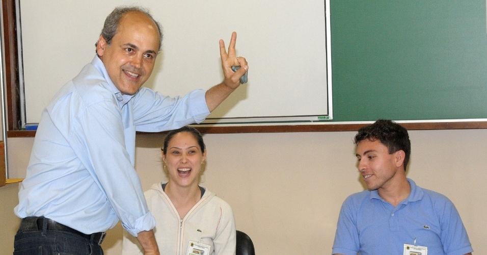 7.out.2012 - O candidato à Prefeitura de Curitiba (PR) pelo PDT, Gustavo Fruet, faz sinal da vitória para os fotógrafos dentro da sua seção eleitoral