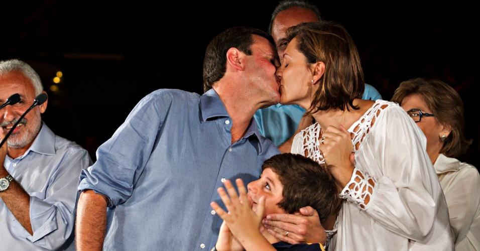 7.out.2012 - Prefeito eleito, Eduardo Paes, beija (outra vez) sua esposa com o filho (abaixo) olhando na comemoração da vitória
