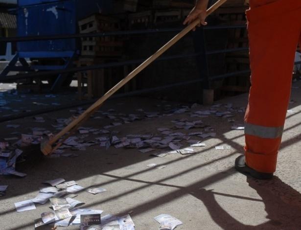 7.out.2012 - Santinhos se acumulam nas principais ruas no Rio de Janeiro, neste domingo (7).  Funcionário limpa a região