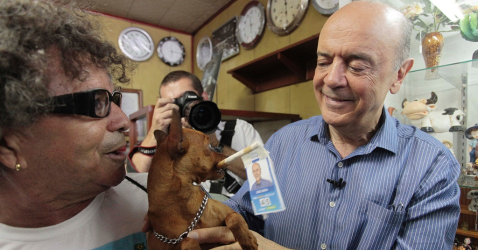 8.out.2012 - O candidato do PSDB à Prefeitura de São Paulo, José Serra, observa o cachorro de nome Gigante, do metalúrgico José da Silva (à esq.), durante caminhada pelo bairro de Vila Formosa, na zona leste da capital, na tarde desta segunda-feira, um dia após o resultado do primeiro turno das eleições municipais. Serra alcançou 30,75% dos votos válidos e disputa o segundo turno com o candidato do PT, Fernando Haddad, que chegou a 28,98%