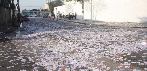 7.out.2012 - A eleitora Barbara Melo registrou rua coberta de santinhos eleitorais em Guarulhos (SP)
