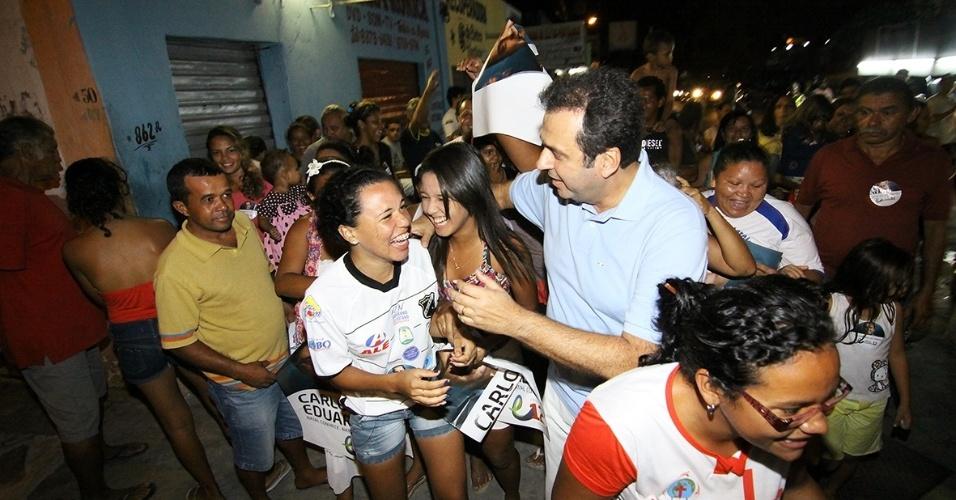 12.out.2012 - Carlos Eduardo (de camisa azul clara), candidato do PDT à Prefeitura de Natal, cumprimenta eleitoras durante caminhada pela zona oeste da capital potiguar