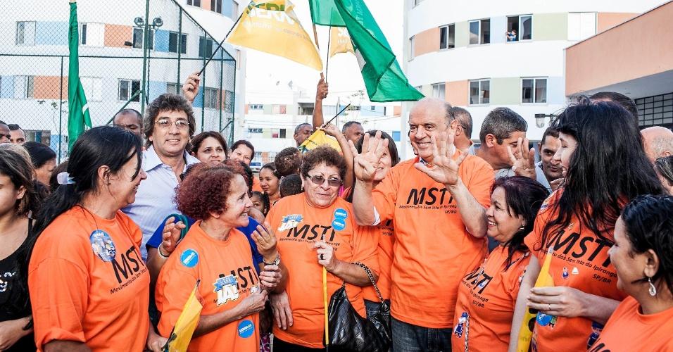 17.out.2012 - Durante caminhada em Heliópolis, zona sul de São Paulo, o candidato do PSDB, José Serra (centro), ganhou uma camiseta do Movimento dos Sem-Teto do Ipiranga (MSTI)