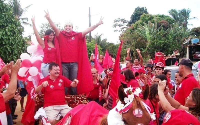 23.out.2012 - João Ribeiro (PMDB), prefeito eleito da cidade de Jacaraú (PB), desfila em carro aberto, segurando um cedro, de manto vermelho e uma coroa de rei