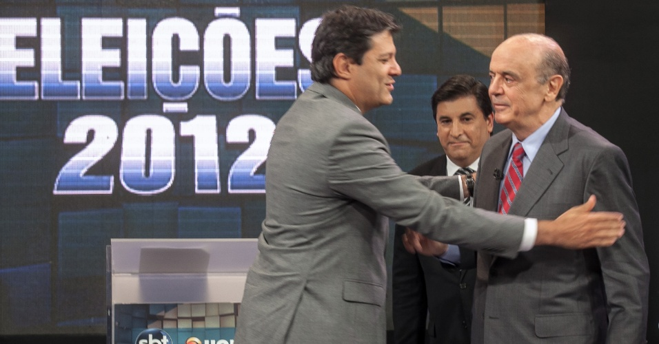24.out.2012 - Os candidatos à Prefeitura de São Paulo, Fernando Haddad (PT) (à esq.) e José Serra (PSDB), se cumprimentam durante o debate promovido pelo UOL e pelo SBT, na sede da emissora, em Osasco (SP), nesta quarta-feira. Assuntos como o mensalão e a terceirização da saúde esquentaram o debate
