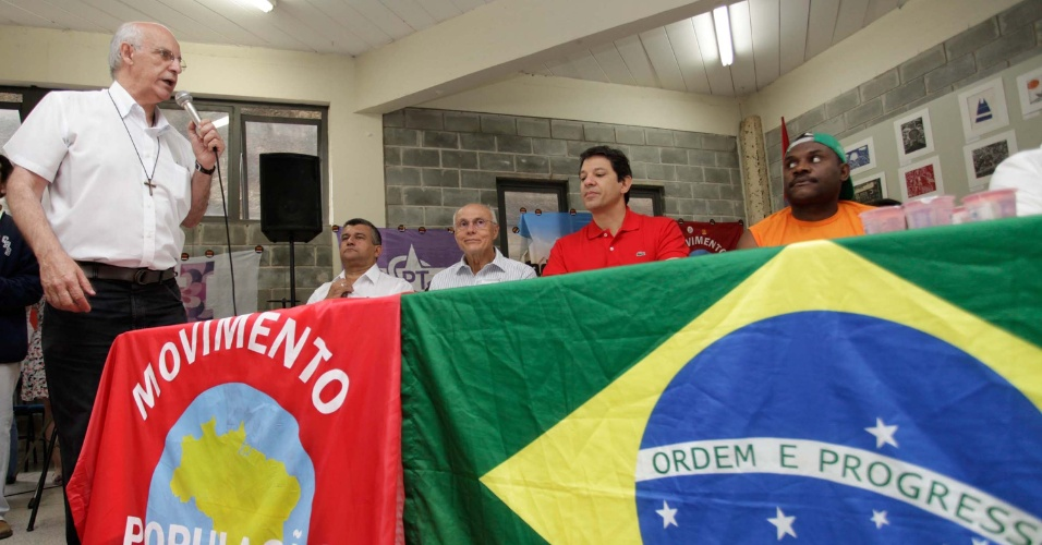 26.out.2012 - Padre Júlio Lancellotti (à esq.) promoveu um encontro entre o candidato do PT à Prefeitura de São Paulo, Fernando Haddad, e moradores de rua, catadores de materiais recicláveis, representantes de camelôs e grupos indígenas na casa de oração do Povo da Rua, na região central da cidade