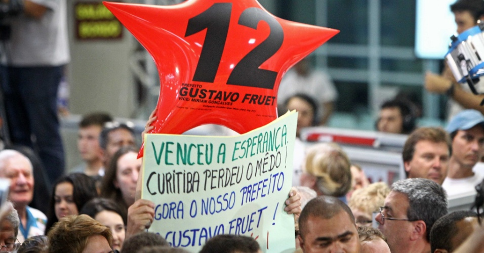 28.out.2012 - Eleitor eleva cartaz e comemora vitória de Gustavo Fruet (PDT) na disputa para a Prefeitura de Curitiba