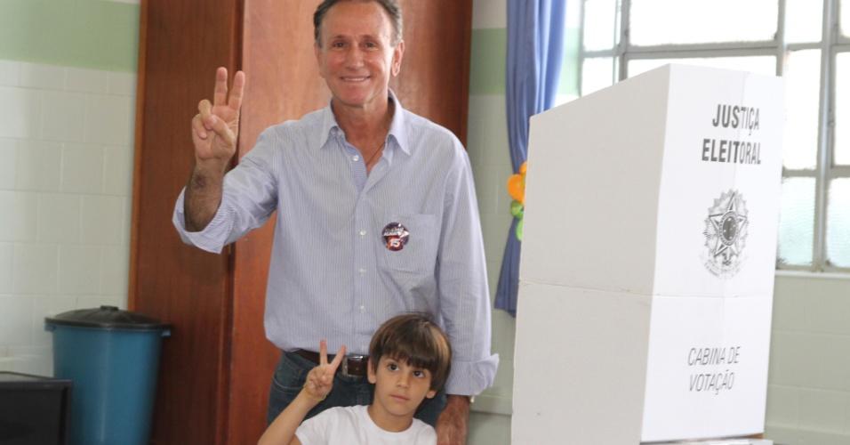 28.out.2012 - O candidato à prefeitura de Uberaba (MG) do PMDB, Paulo Piau, vota no colégio Marista acompanhado do neto, neste domingo (28)