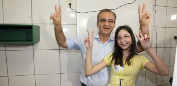 28.out.2012 - O candidato do PSDB à Prefeitura de Teresina (PI), Firmino Filho, faz sinal de vitoria com a filha Cristina após votar no Colégio Sinopse, neste domingo (28)