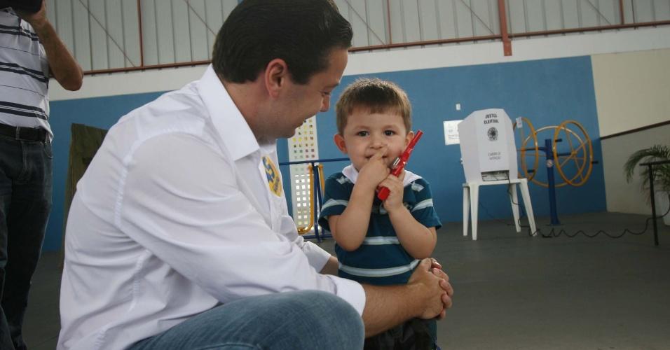 28.out.2012 - O candidato do PSDB eleito à Prefeitura de Blumenau (SC), Napoleão Bernardes Neto, leva filho para votar neste domingo (28)