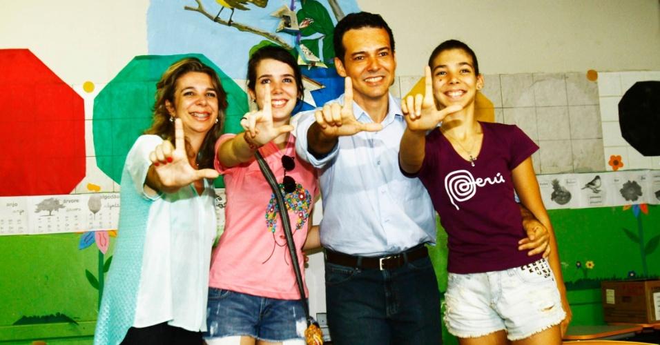 """28.out.2012 - O candidato do PT à Prefeitura de Cuiabá (MT), Lúdio Cabral, faz o sinal do """"L"""" aos fotógrafos com a família após votar na escola Quintino Pereira de Freitas, no bairro Canjica, neste domingo (28)"""