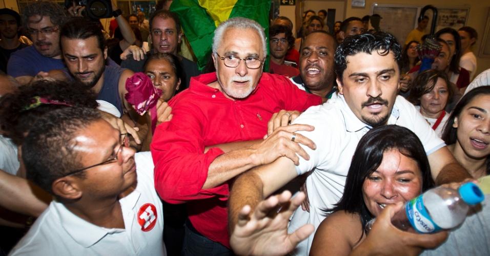 28.out.2012 - O ex-presidente do PT José Genoino (de vermelho) , condenado por dois crimes no julgamento do mensalão, votou por volta das 16h15, cercado por quase 40 militantes petistas. O grupo formou um cordão de isolamento e quebrou equipamentos de jornalistas que tentavam entrevistá-lo. Genoino repetiu palavras de ordem e sorriu abraçado a uma bandeira do Brasil