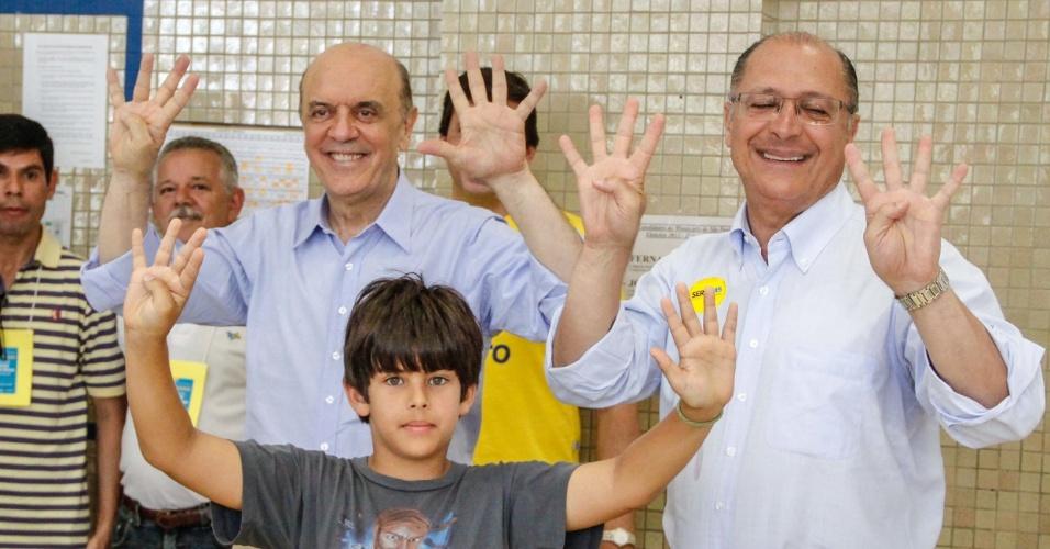 28.out.2012 - O governador Geraldo Alckmin (PSDB) acabou confundindo 44 com 45 (número do PSDB). Alckmin acompanhou o candidato tucano José Serra (à esquerda), que estava com o neto, em votação em colégio da zona oeste da capital paulista, neste domingo (28)
