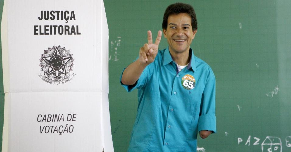 28.out.212 - O candidato do PCdoB à Prefeitura de Contagem (MG), Carlin Moura, vota na manhã deste domingo (28) - ele foi acompanhado da mãe, Dona Fiotinha, à zona eleitoral