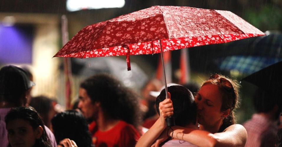 28.out.2012 - Casal comemora eleição de Fernando Haddad (PT) à Prefeitura de São Paulo na noite deste domingo, na avenida Paulista, embaixo de chuva. Haddad foi eleito com 55% dos votos, contra José Serra (PSDB), que teve 44%