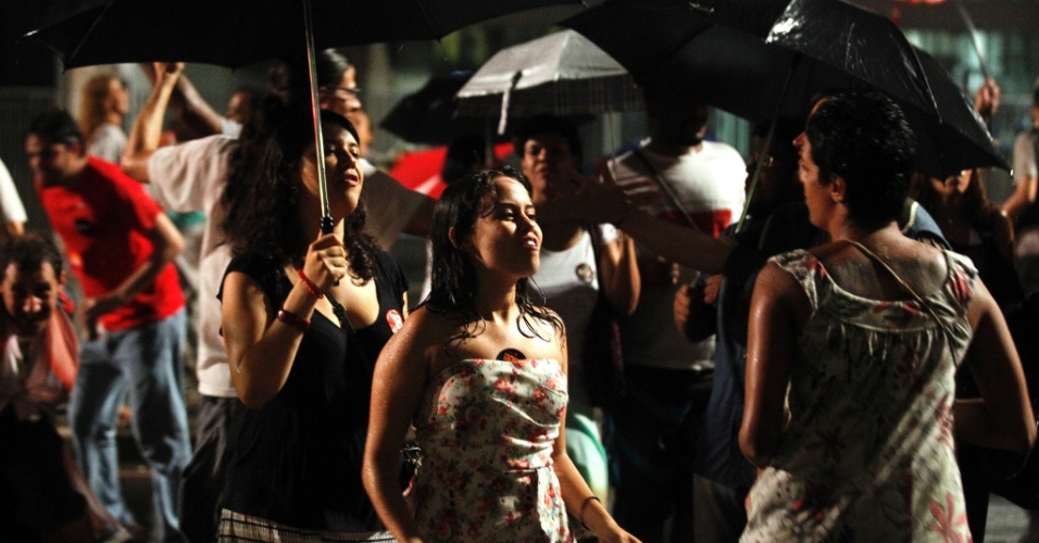 """28.out.2012 - Embaixo de chuva na avenida Paulista, militantes do PT comemoram eleição de Fernando Haddad (PT) à Prefeitura de São Paulo na noite deste domingo. Haddad recebeu 55% dos votos e José Serra, 44%. Em palco montado na avenida, Haddad disse em discurso que """"as forças adormecidas do progresso, da tolerância e da igualdade foram acordadas hoje na cidade de São Paulo"""""""